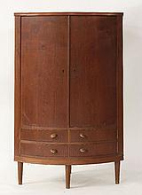 A Danish teak bow front corner cupboard,  the cupboard over four hinged drawers on four turned l