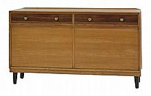 A Gordon Russell ash and walnut sideboard,  the plain top over two drawers and two drop down cup
