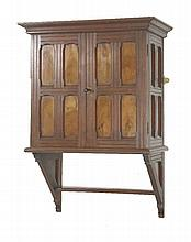 A walnut wall cabinet,  in the style of E W Godwin, late 19th century, with panelled doors and s