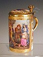 A Vienna style porcelain lidded mug, with a painted panel and lid, and brass finger thumb piece plinth in the form of a crown, with a painted inscription 'Tele Wach And Der Insel Calipso', and a blue underglaze mark, 13cm
