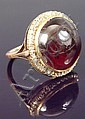 A cabochon garnet and diamond ring, the circular