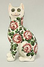 A Wemyss 'Cabbage Roses' cat, with glass eyes,