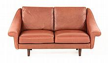 A brown leather settee, with stitched cushions, on