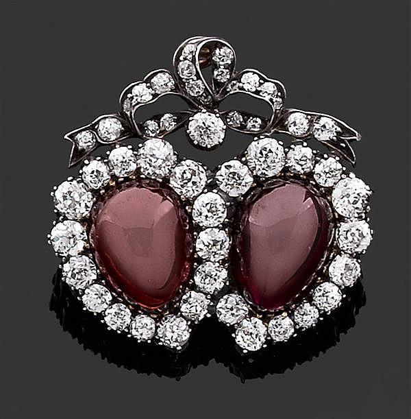 Broche composée de deux cœurs enrubannés ornés en leur centre d'un cabochon de grenat de forme poire entouré de diamants taille bril...
