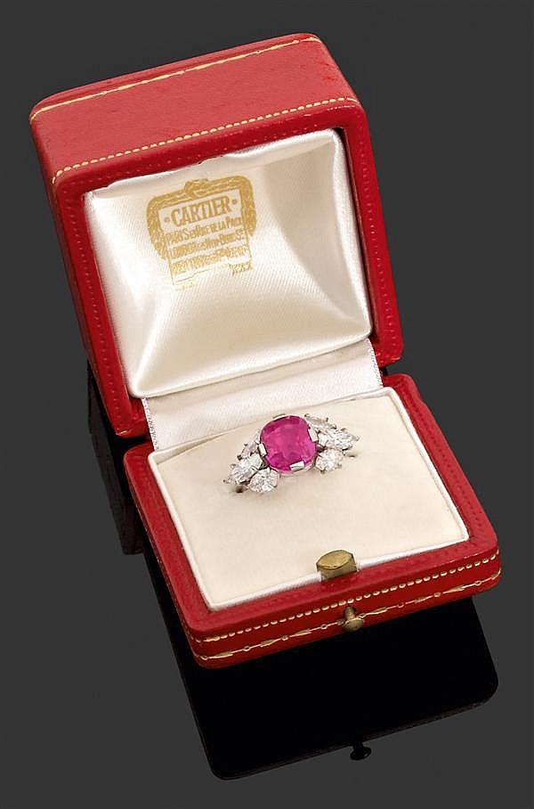 CARTIER Années 60 Importante bague rubis en platine et or gris. Elle est sertie d'un rubis coussin en chaton à griffes encadré par s...