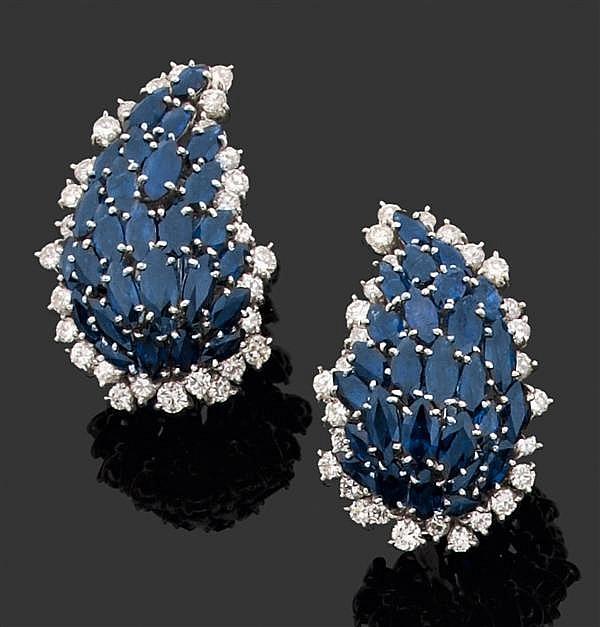 Paire de Clips d'oreilles en or gris, de forme piriforme bombée. Ils sont sertis de saphirs navette dans un entourage de diamants ta...