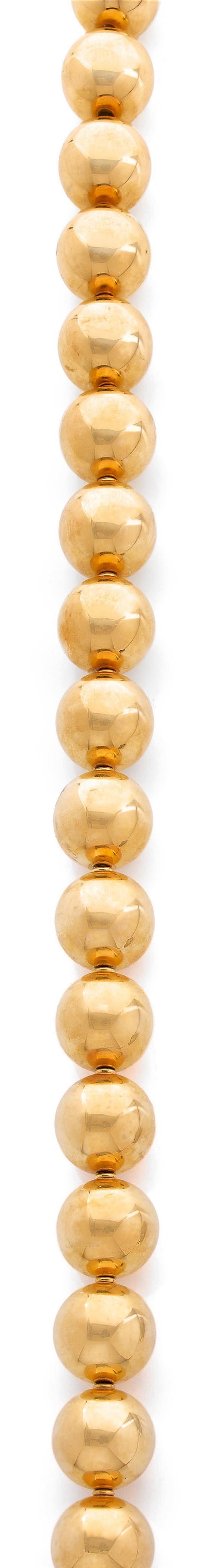 Important collier composé de boules d'or jaune uni de diamètres égaux montées sur une chaîne. Les boules sont séparées par des petit...