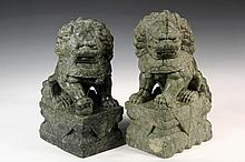 PAIR OF CHINESE HARDSTONE SCULPTURES - Guardian Foo Dogs on integral plinths, in green stone with a black matrix, having opposing stanc
