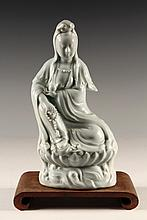BLANC DE CHINE FIGURE - Chinese Seated Quan Yin, enthroned on a lotus base, 18th c, in pale celadon glaze, with impressed seal on under