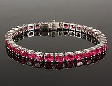 BRACELET - Platinum and Oval Ruby Line Bracelet, composed of thirty-four oval brilliant cut rubies set in four prong links completed by