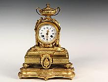 FRENCH MANTEL CLOCK - Guiche Palais Royale Model 147  Louis XV-style gilt bronze figural time and strike clock with porcelain dial, set on the original conforming gilt plateau