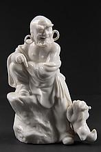 CHINESE PORCELAIN FIGURE - Blanc de Chine Standing Immortal with large loop earrings, reacting to foo dog leaping up at his leg, impres