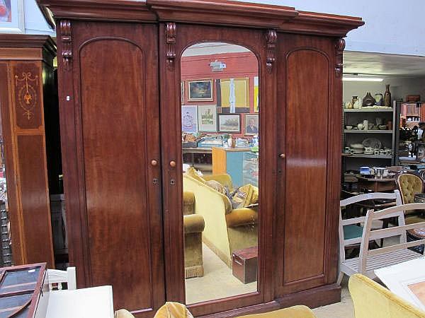 A mid Victorian mahogany triple wardrobe, stamped
