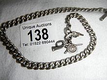 A silver military chain with canon, gun and bugle