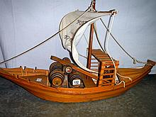A large wooden replica boat with barrels