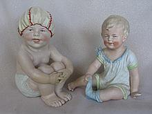 Two seated Heubach type bisque Piano Babies with number marks:- 20cm boy with shower cap with finger