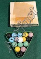 Early set of of child's pool balls in a metal rack.