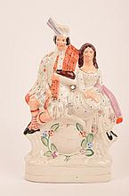 English Staffordshire figurine of a man and lady sittting.