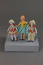 THREE GERMAN ALL BISQUE DOLLHOUSE DOLLS INCLUDING BOY/GIRL PAIR DRESSED IN FELT, AND PAINTED BISQUE GIRL.