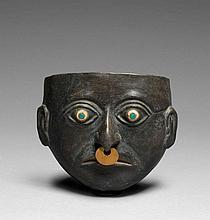 RÉCIPIENT DÉCORÉ D'UN MASQUE D'HOMME Culture Mochica, Nord du Pérou 200-500 après J.-C. Céramique noire à surface vernissée légèreme.