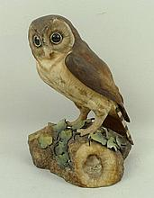 A Royal Crown Derby bone china owl, raised on a