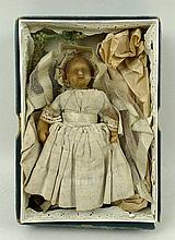 A Victorian wax doll, missing legs, fully clothed,