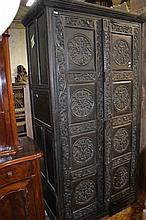A carved timber two door linen press with panelled sides