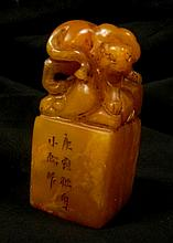 A carved orange stone seal with wild cat to top