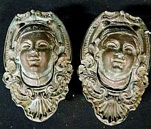 A pair of bronze decorative door knockers in the form of a face