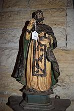 A timber carved religious figure on pedestal