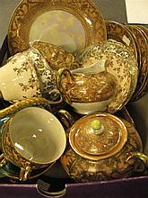 A collection of gold gilt and pearlescent teaware and decorative wall plates