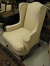 A vintage wing chair with cream upholstery