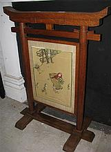 An antique oak Arts and Crafts fire screen in oriental theme with needle work panel
