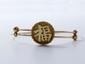 Bracelet en or 9 k, orné d'un disque gravé d'un idéogramme asiatique, avec système d'ouverture à glissière. (déformations). Poids: 9.10 g.
