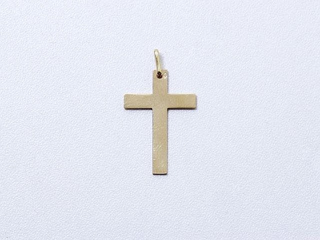 Pendentif croix en or, une face guillochée. . Poids: 1.50 g.