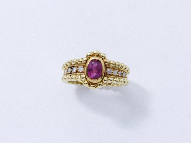 Bague en or, ornée d'un rubis ovale en serti clos, épaulé de diamants brillantés dans un décor perlé.. Poids brut: 7.80 g. TDD: 51. (égrisures)