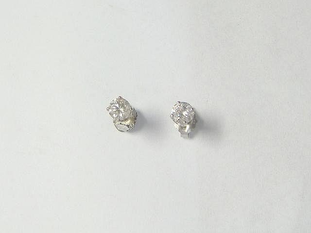 Paire de clous d'oreilles en or gris 14 k, ornés de diamants brillantés en serti griffe.. Poids des diamants: 0.50 ct env l'ensemble.. Poids brut: 0.90 g.