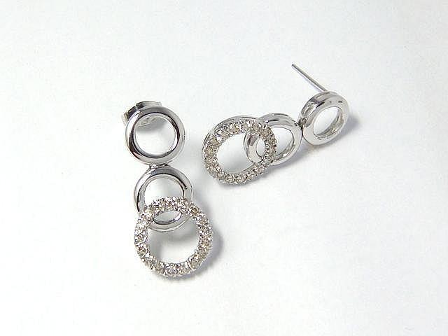 Paire de pendants d'oreilles en or gris, stylisant une chute d'anneaux, le dernier rehaussé de diamants brillantés. (manque une poussette). Poids brut: 7.6 g. Haut: 2.9 cm.