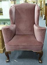 A wing back armchair on carved cabriole legs