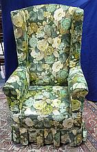 A porter's upholstered wing back chair on a square
