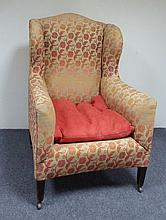 A wing back armchair on square taper legs