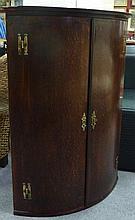 A George III oak bow front hanging corner cupboard