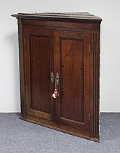 A George III oak hanging corner cupboard, the pane
