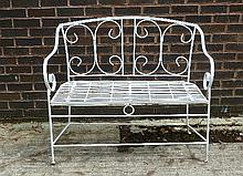 A wrought iron garden seat with slatted seat and