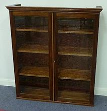 A mahogany wall cabinet with glazed door, by E C