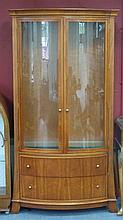 A bowfront display cabinet by Wade, the upper