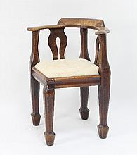A Cotswold Arts & Crafts oak corner armchair, with