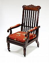 A George IV mahogany campaign chair with scroll