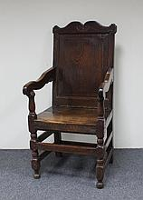 An oak panel back armchair with shaped cresting