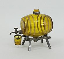 A yellow glass spirit barrel on a plated stand,